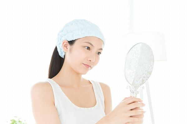 手鏡をみる女性