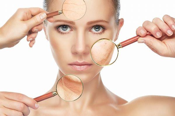 虫眼鏡で肌を拡大する女性